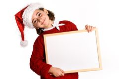 Little girl wearing santa hat holding blank board. For advertisementon on white background.    Invitation to christmas activities. Winter clothes Stock Photos