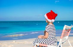 Little girl wearing Santa hat during tropical Royalty Free Stock Image