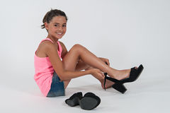 Little girl wearing the shoes of mom Stock Photography