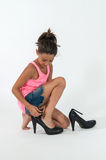 Little girl wearing the shoes of mom Royalty Free Stock Images