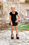 Little girl wearing shoes and standing on the road in the city Stock Image