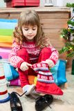 Little girl wearing soft red fur boots on the floor at Christmas Eve Royalty Free Stock Photos