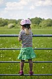 Little girl wearing a striped t-shirt, green skirt and a pink bicycle helmet standing on a field gate looking out over a green fie Stock Image
