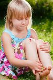 Child with wounded knee looking at aching place in a summer garden stock images