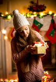 Little girl wearing sweater looking in gift box at Christmas eve Stock Photo