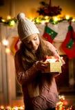 Little girl wearing sweater looking in gift box at Christmas eve. Cute little girl wearing sweater looking in gift box at Christmas eve Stock Photo