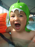 Little girl wearing a swimming cap. Little asian girl wearing a monster swimming cap in a swimming pool Stock Photos
