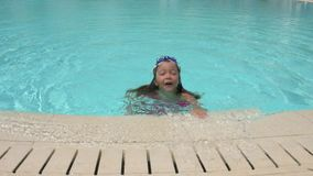 Little girl playing in swimming pool. Little girl wearing swimming glasses in swimming pool stock footage
