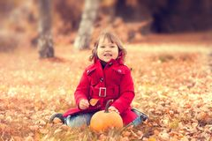 Little girl wearing warm red coat having fun in the autumn park. Stock Photo