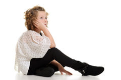 Little girl wearing white top and black pants sitt Stock Images