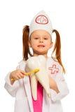 Little girl wearing whites brushing tooth model Stock Photos