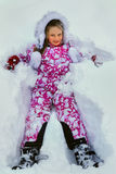 Little girl wearing winter clothes lying in  snow Stock Photos