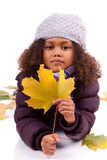 Little girl wearing winter clothes playing with le Stock Images