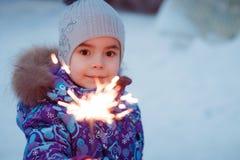 Little girl wearing winter jacket is standing with bengal light. Smiling little girl wearing winter jacket is standing with bengal light Stock Photo