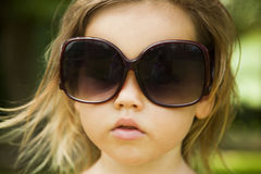 Little girl wears a large adult sunglasses Royalty Free Stock Photo