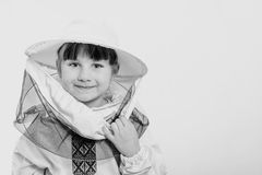 A little girl wears an over sized bee suit in studio white background. Black and white Royalty Free Stock Photography