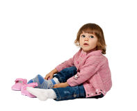 Little girl wears shoes on a white floor Royalty Free Stock Image