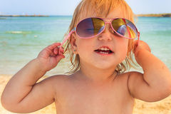 The little girl wears sunglasses and laughs Royalty Free Stock Photography