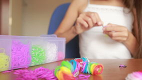 Little girl weave wristband of rubber bands. Colored rubber bands for weaving. Little girl weave wristband of rubber bands. Wave Rainbow loom Colored rubber stock footage