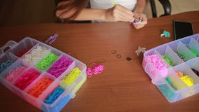 Little girl weave wristband of rubber bands. Colored rubber bands for weaving. Little girl weave wristband of rubber bands. Wave Rainbow loom Colored rubber stock video