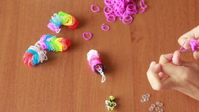 Little girl weave wristband of rubber bands. Colored rubber bands for weaving. Little girl weave wristband of rubber bands. Wave Rainbow loom Colored rubber stock video footage