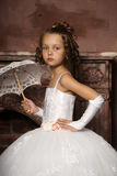 Little girl in wedding dress. Girl in white dress next to the fireplace Royalty Free Stock Photo
