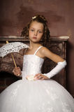 Little girl in wedding dress. Girl in white dress next to the fireplace Stock Image