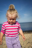 Little girl weeping by the sea. Stock Images