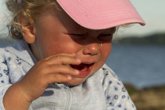 Little girl weeping by the sea. Stock Photo