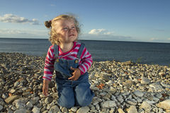 Little girl weeping by the sea. Stock Image