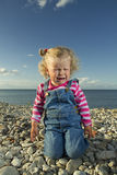 Little girl weeping by the sea. Stock Photos