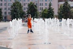 Little girl in wet dress roller skates in fountain in summ. Happy little girl in wet dress roller skates in fountain in summer city Stock Image