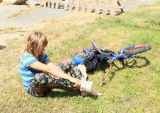 Little girl in wet pants. Little girl - barefoot kid in wet pants sitting in front of her bicycle and dressing up shoes Stock Image