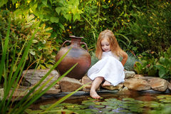 Little girl wets feet in a pond with lilies Stock Photos