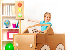 Little girl at the wheel of handmade cardboard car. Smiling four years old girl at the wheel of handmade cardboard car pointing to the toy traffic light by her Royalty Free Stock Images