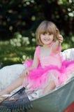 Little girl in wheelbarrow Stock Images