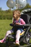 A little girl in a wheelchair laughs loudly. stock images