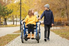 Little girl in wheelchair with brother. Outdoors stock images