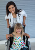 Little girl on a wheelchair with her doctor Stock Images