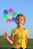 Little girl with whirligig sits at grass Royalty Free Stock Photography