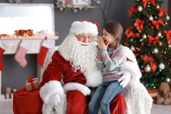 Cute girl whispering in authentic Santa Claus` ear indoors. Little girl whispering in authentic Santa Claus` ear indoors stock photography