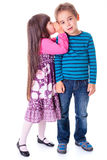 Little girl whispering into boy's ear Royalty Free Stock Photography