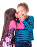 Little girl whispering into boy's ear Stock Images