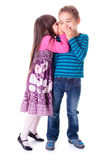 Little girl whispering into boy's ear Stock Photography