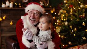 Little girl whispering Santa Claus ear her christmas wish sitting on his laps,