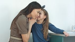 Little girl whispering secret in her mommy`s ear at the doctor`s royalty free stock photos