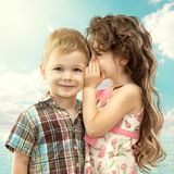 Little girl whispering something to boy. On blue sky. Love concept Stock Images