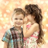 Little girl whispering something to boy. Love concept Royalty Free Stock Images