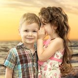 Little girl whispering something to boy. On sea landscape at sunset. Love concept Royalty Free Stock Image