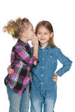 Little girl whispers something to her friend Royalty Free Stock Images